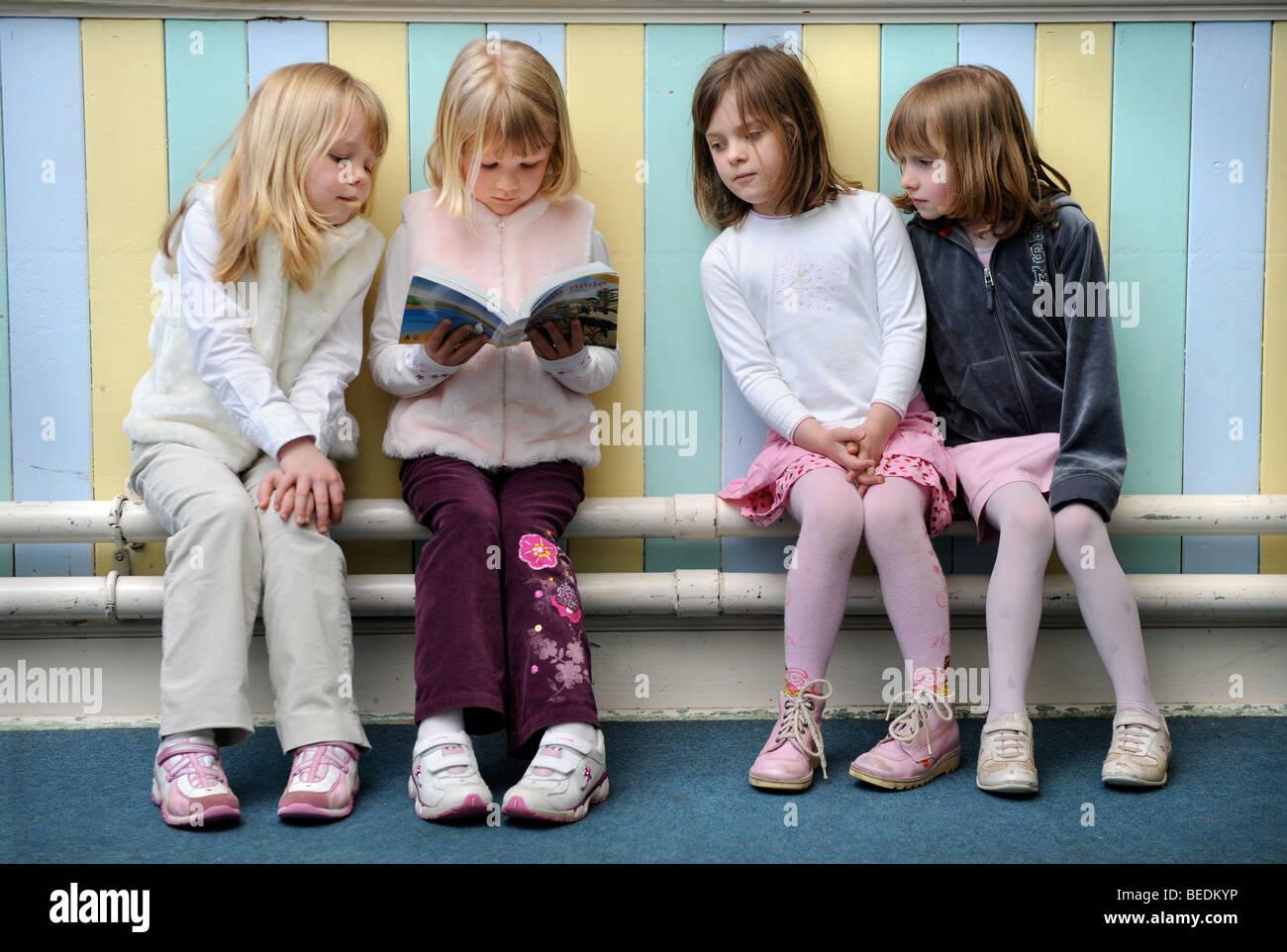 Un GROUPE DE QUATRE FILLES LA LECTURE D'UNE BIBLE ENSEMBLE À UNE ÉCOLE DU DIMANCHE UK Photo Stock