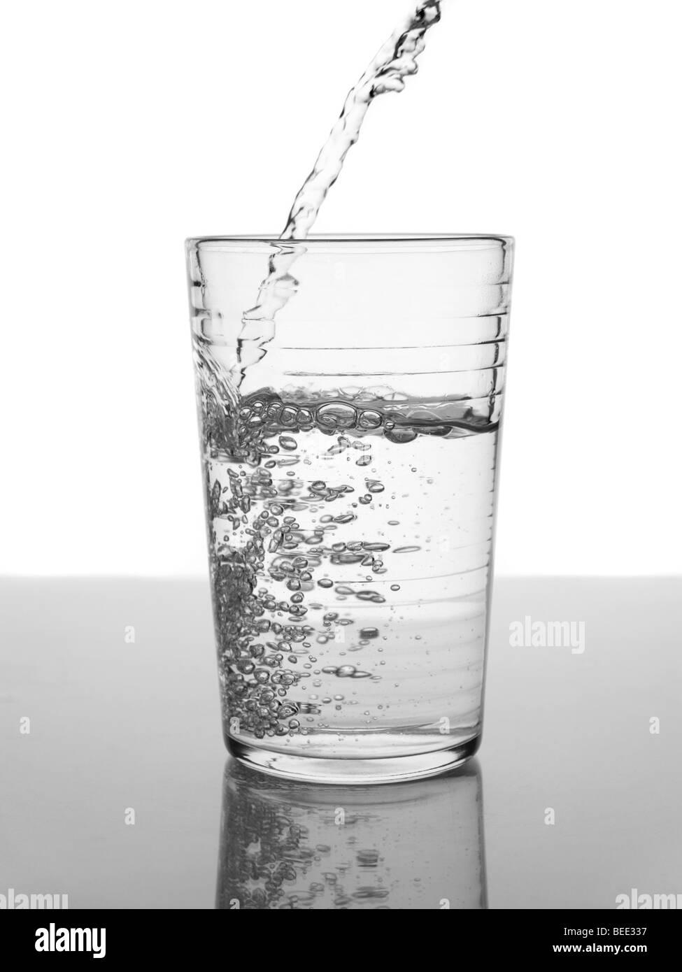 On verse de l'eau dans un verre. Banque D'Images