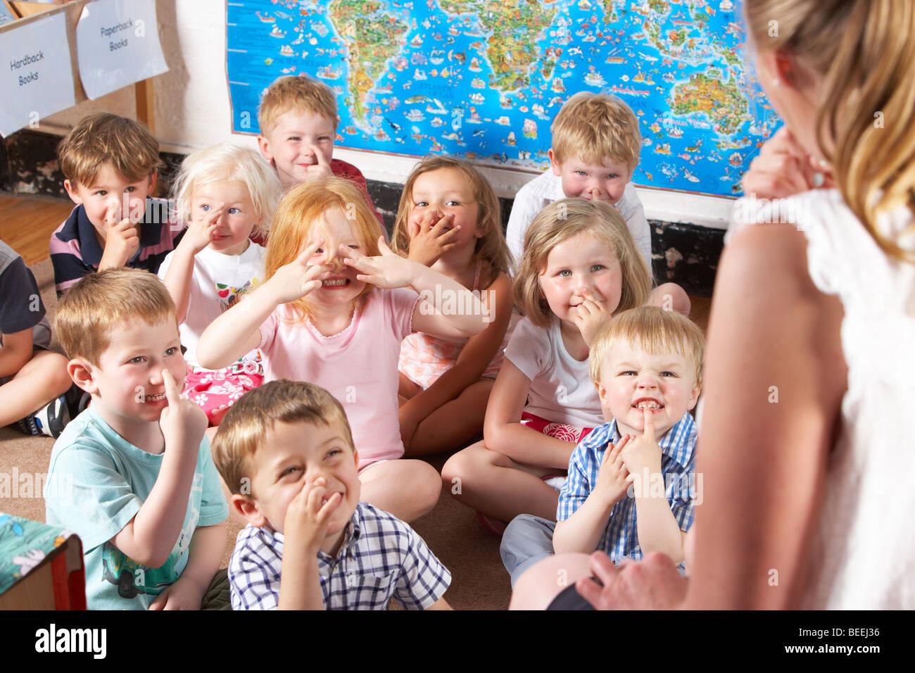 L'écoute de la classe préscolaire Montessori/à l'enseignant sur un tapis Photo Stock