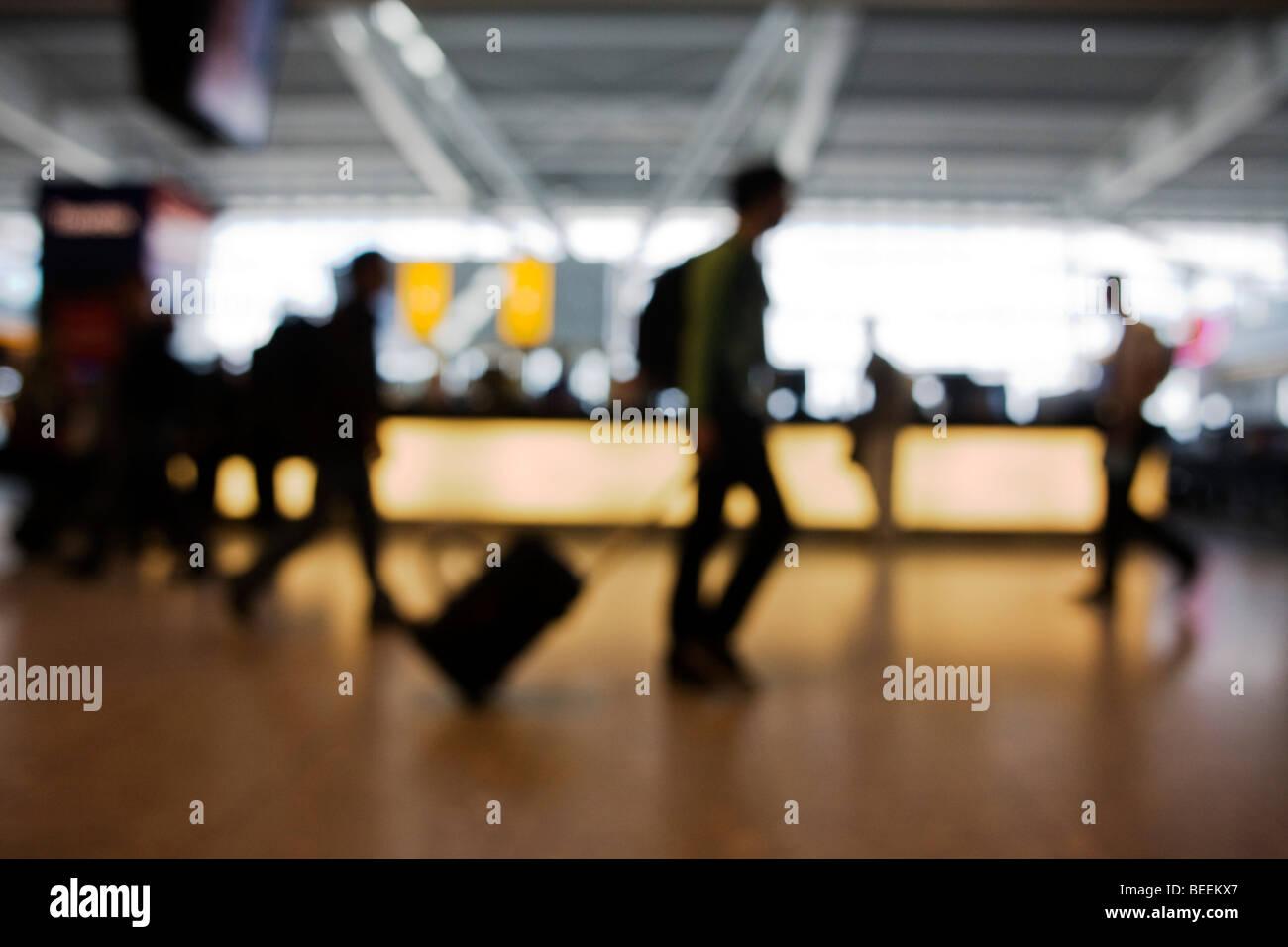 Hors focale, anonyme de passagers transitent par contre une forte lumière arrière de départs à Photo Stock