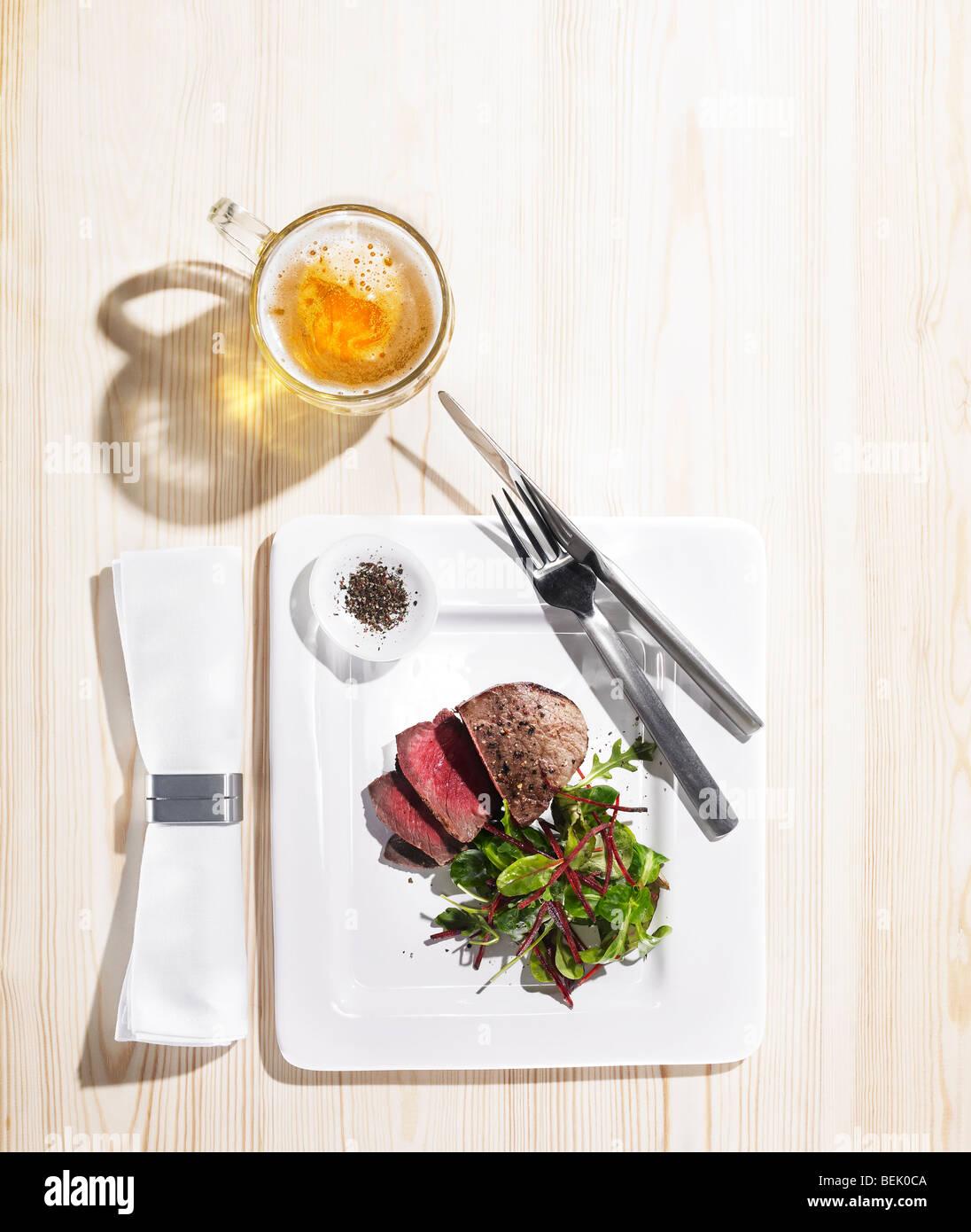 Rôti de bœuf servi avec une salade d'épinards et betteraves, de poivre noir et d'une pinte de bière Banque D'Images