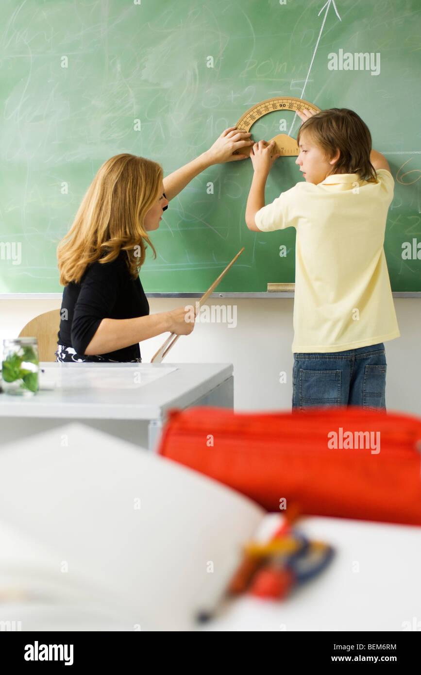 Élève d'école élémentaire l'enseignant montrant comment dessiner l'angle à l'aide d'angles Banque D'Images