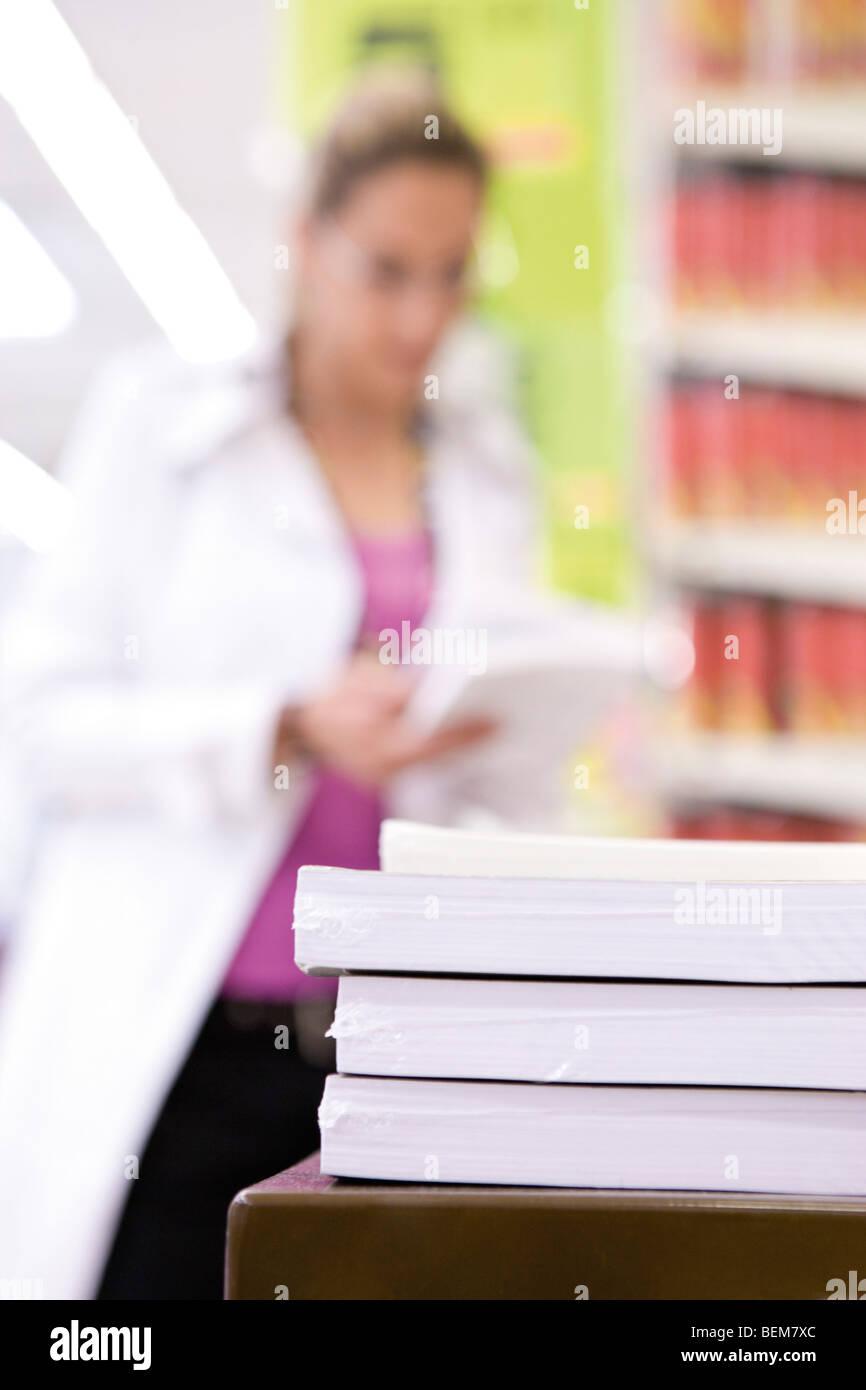 Rames de papier en pile, shopper in background Banque D'Images