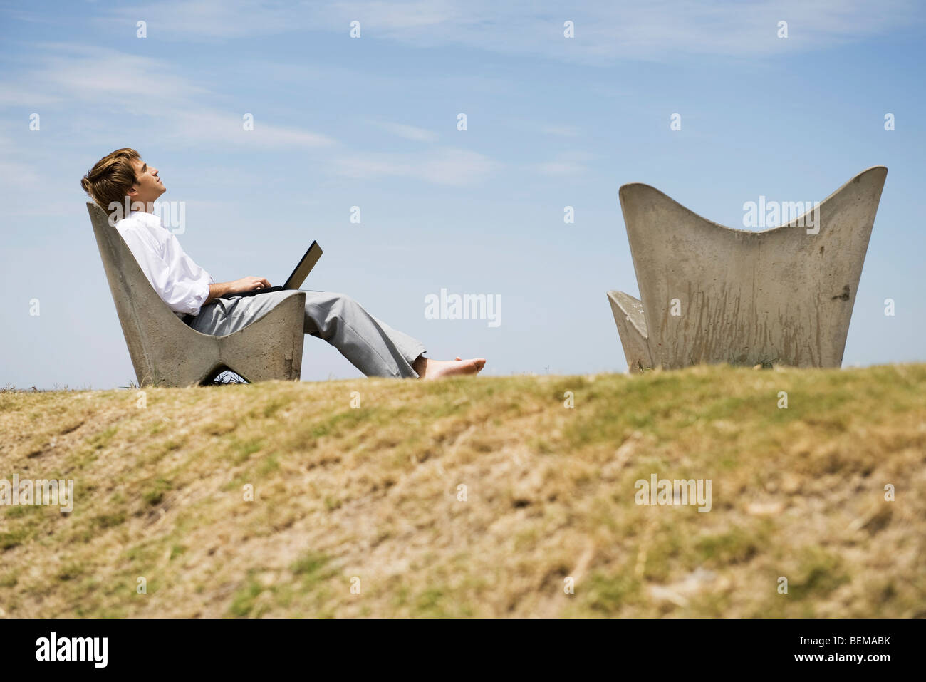 Man with laptop computer outdoors, daydreaming Photo Stock