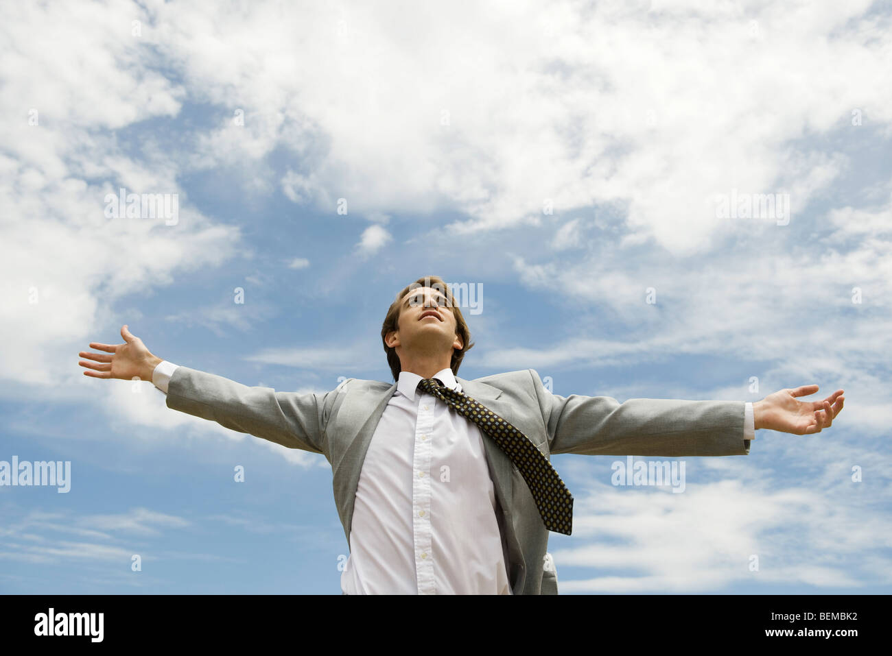 Businessman with arms outstretched contre ciel nuageux Photo Stock