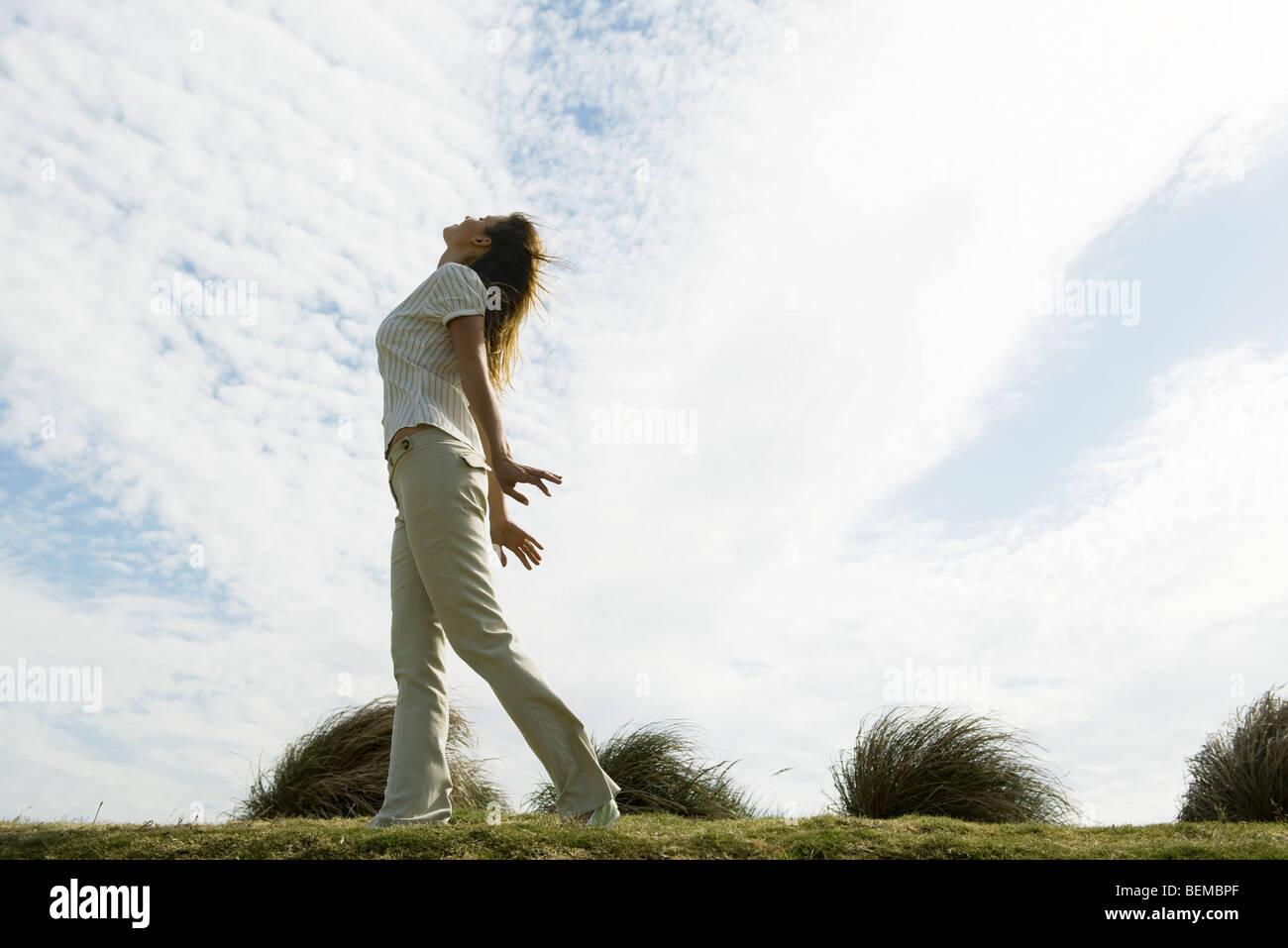 Femme à l'extérieur debout avec les bras, tête en arrière Photo Stock