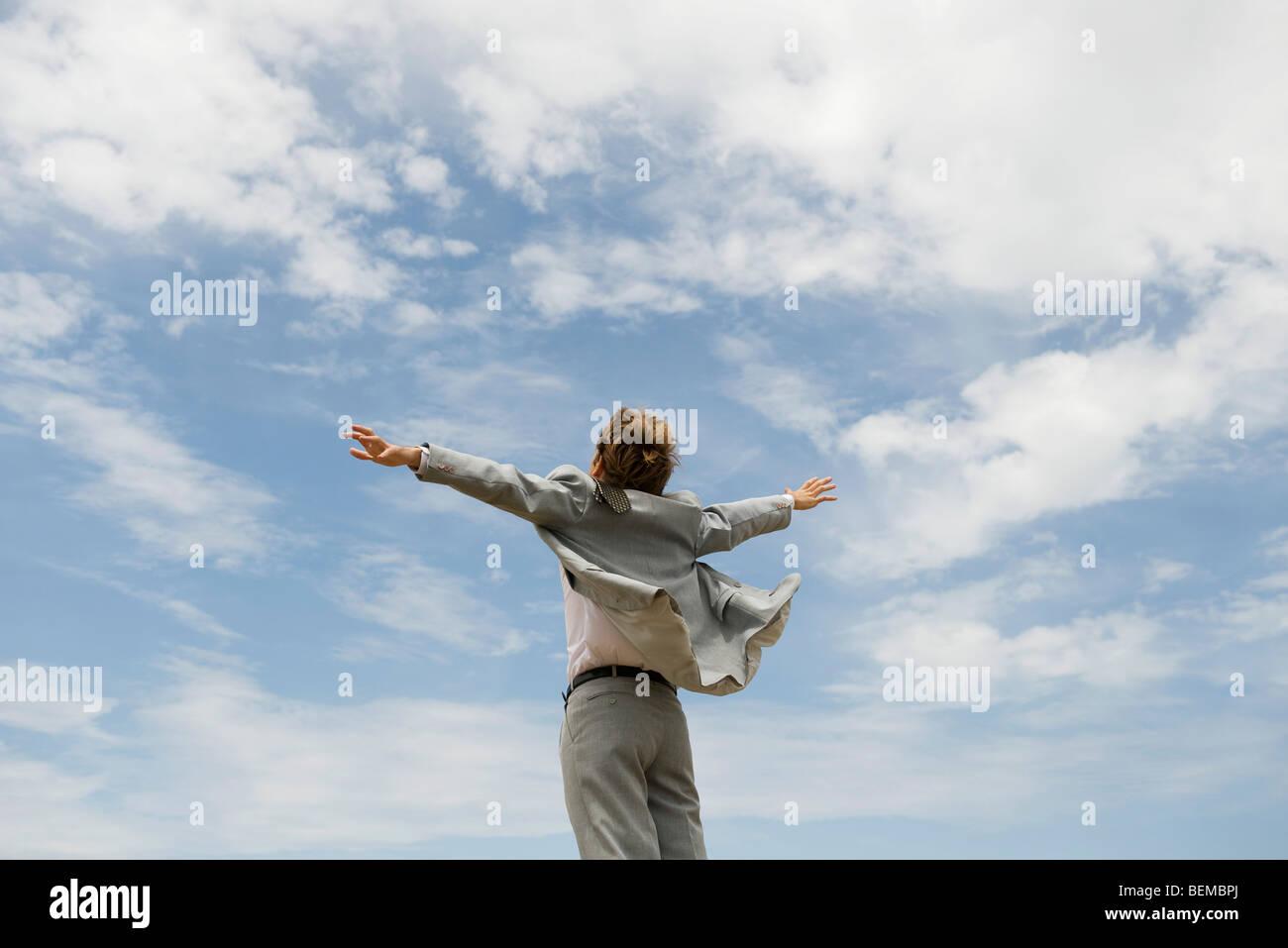 Businessman with arms outstretched contre ciel nuageux, vue arrière Photo Stock