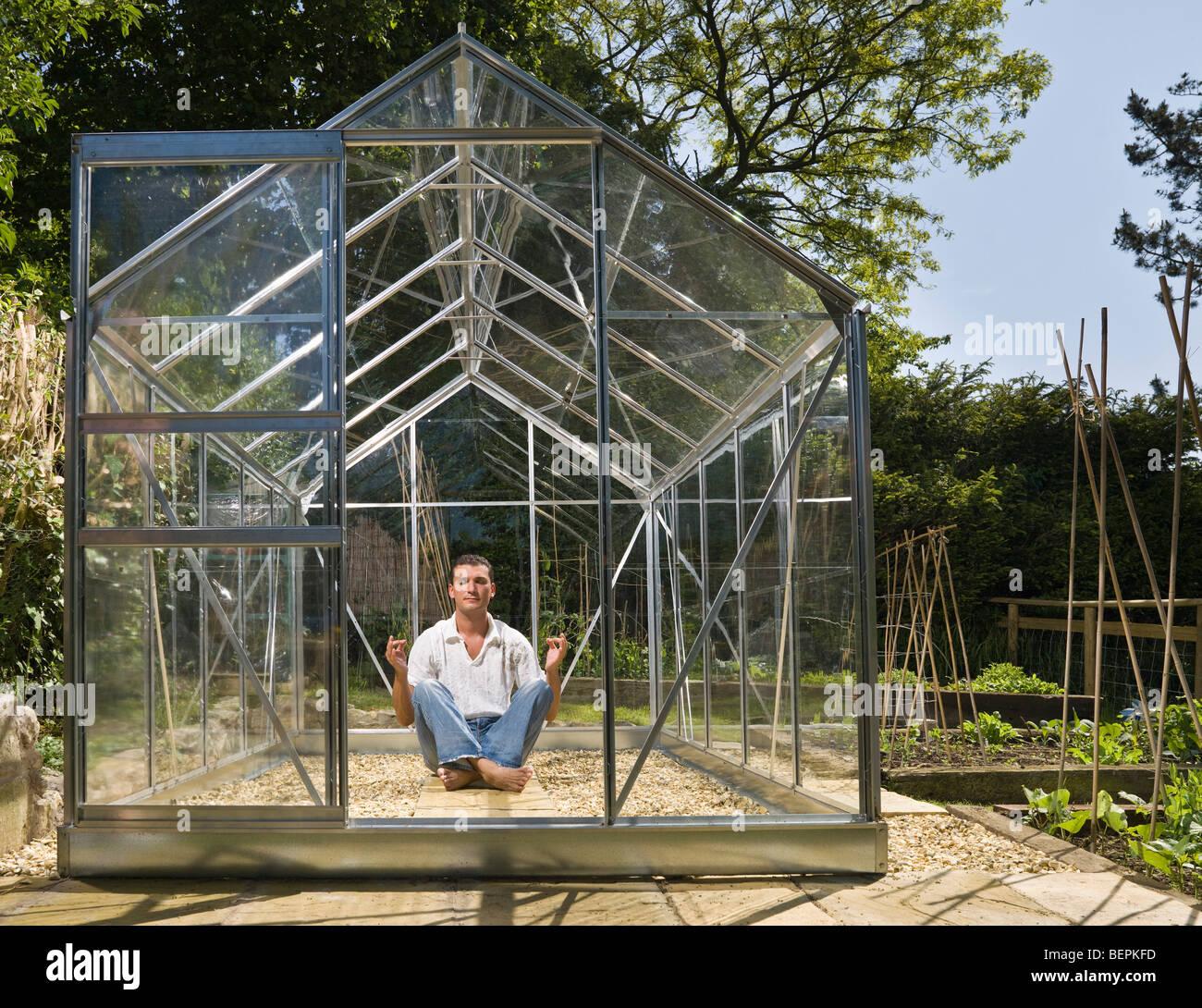 Homme méditant dans serre de jardin Photo Stock