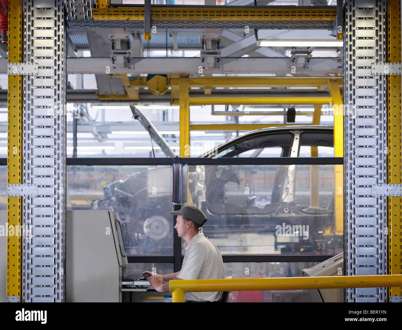 Travailleur sur les contrôles sur ligne de production Photo Stock
