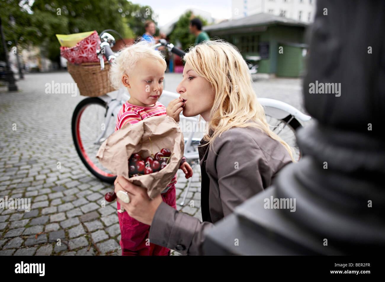 Petite fille et mère de manger des cerises Banque D'Images