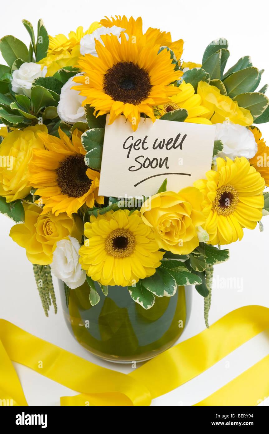 Un vase avec des fleurs et une carte de prompt rétablissement. Photo Stock