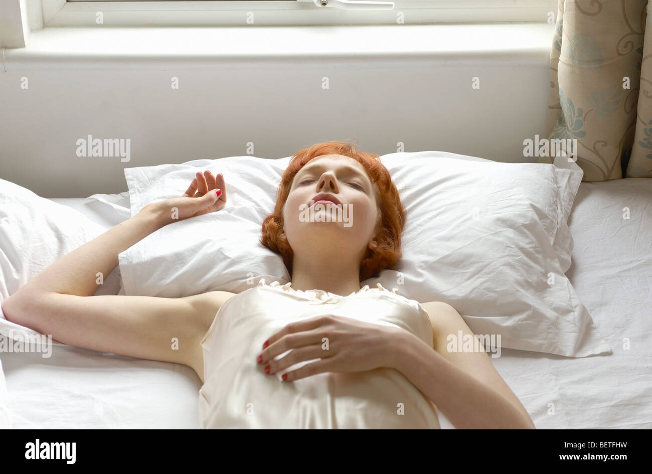 Woman asleep on bed Photo Stock