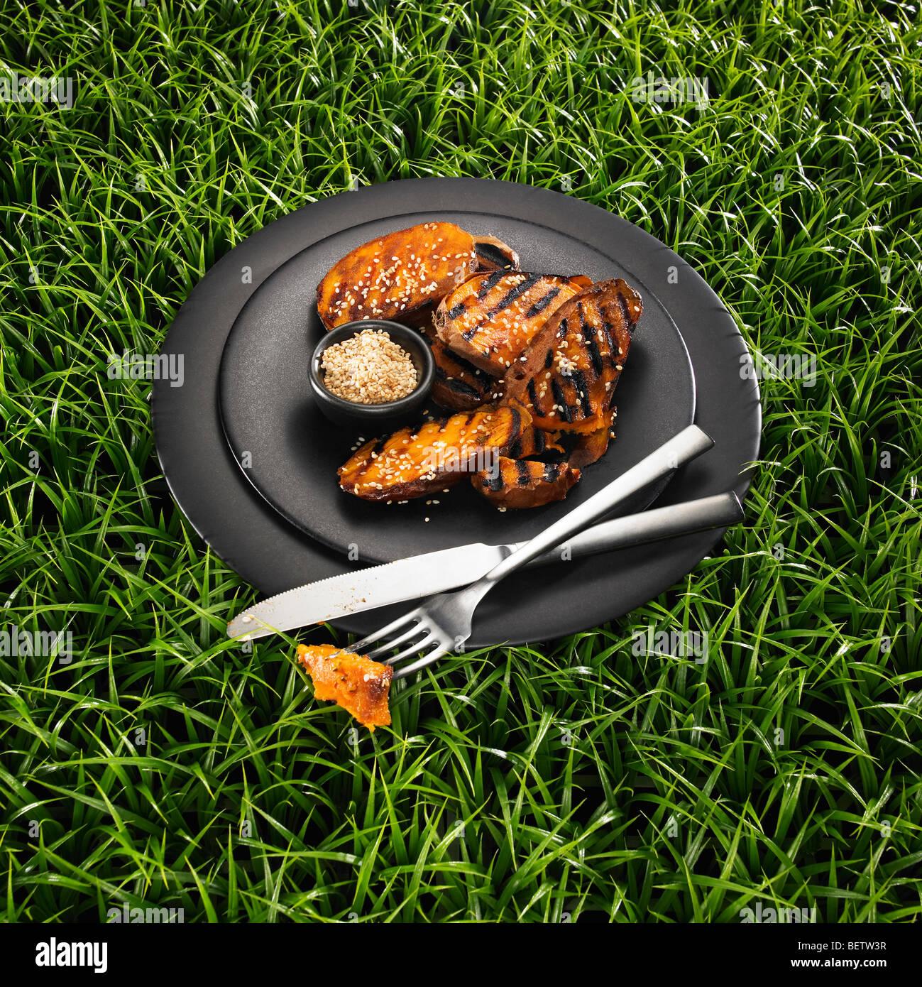 La patate douce, sauce aux graines de sésame sur une plaque noire et un fond d'herbe. Photo Stock