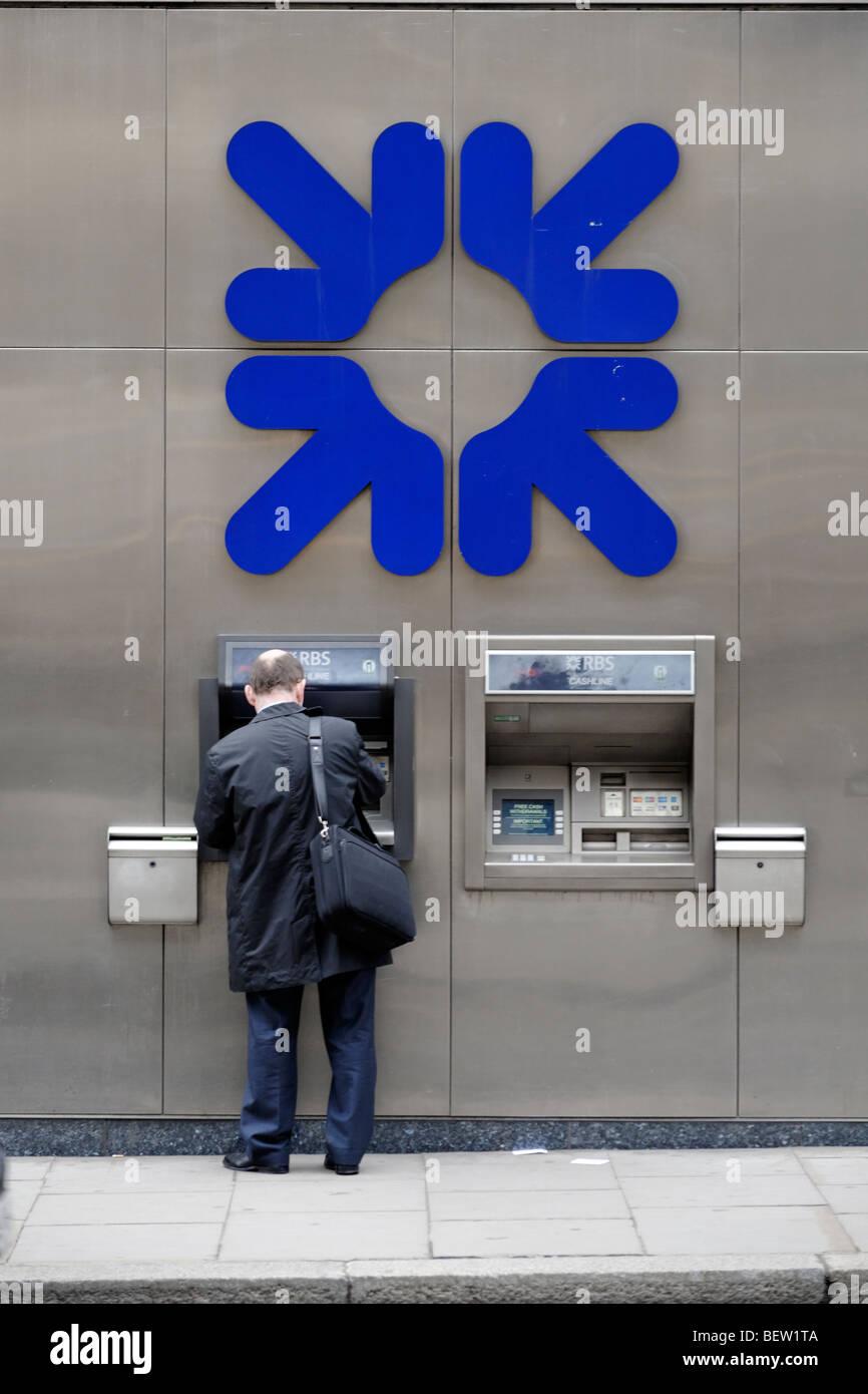 Retirer de l'argent de l'homme point trésorerie RBS machine. Londres. La Grande-Bretagne. UK Banque D'Images
