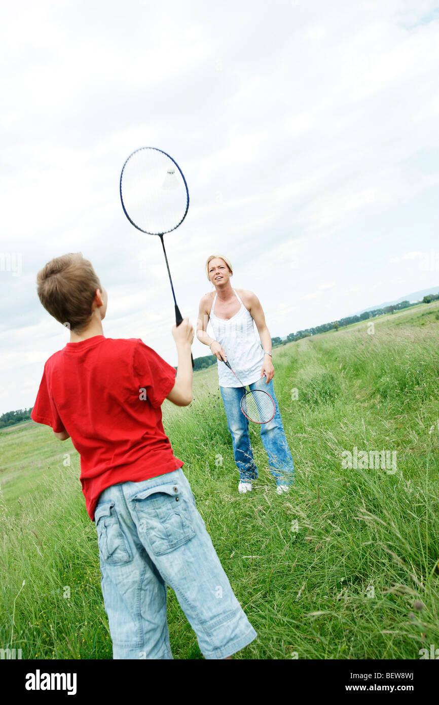 Mère et son fils jouer au badminton sur un pré Photo Stock