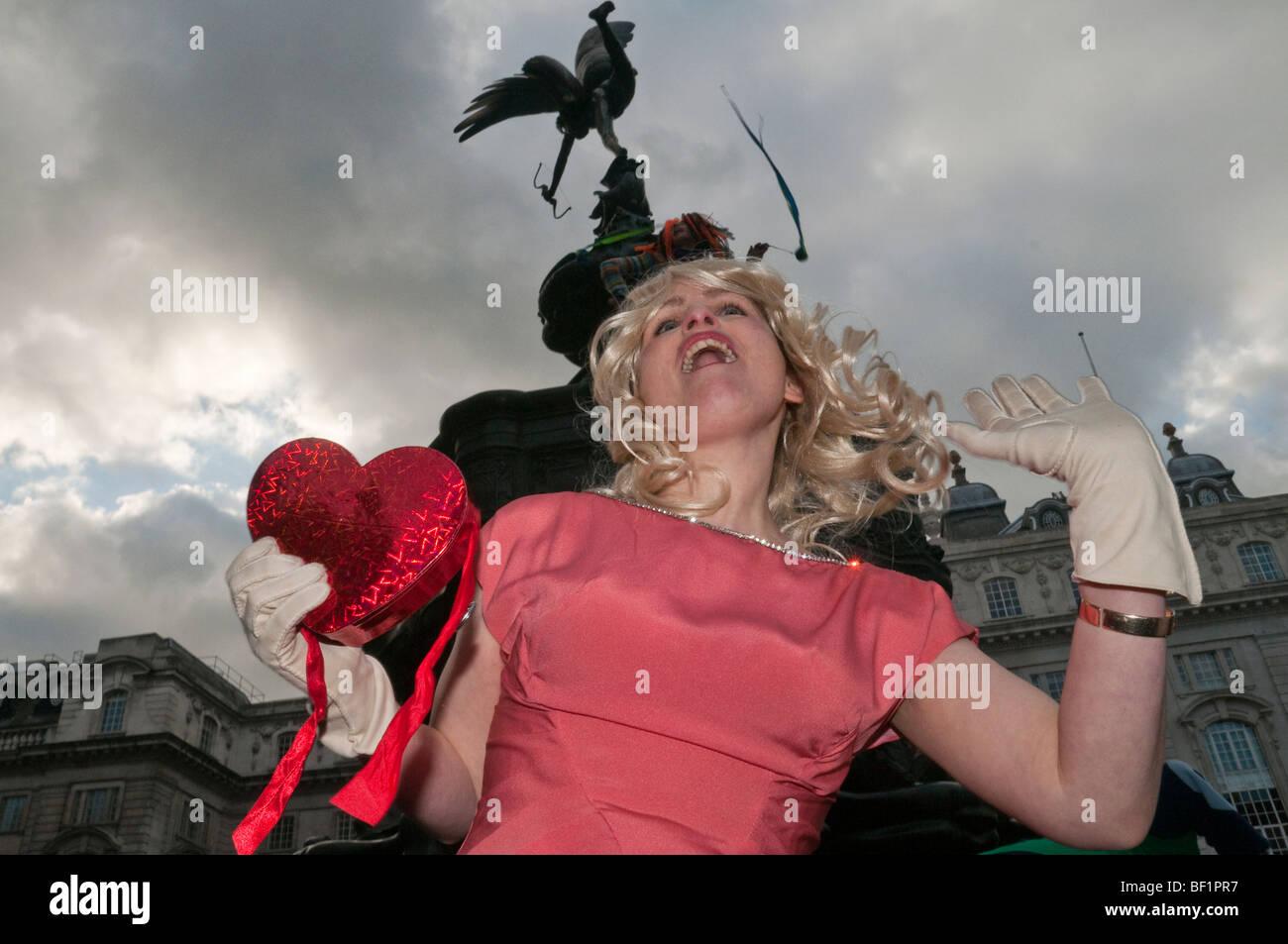 Récupérer l'amour Parti Valentines à Piccadilly Circus, célèbre l'amour contre le consumérisme. Femme avec coeur et Eros Banque D'Images