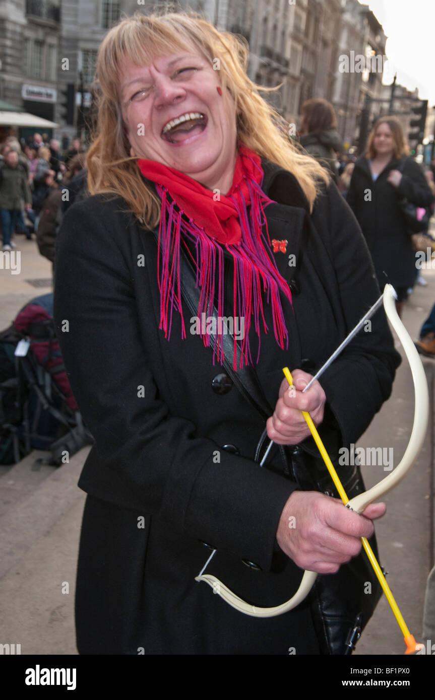 Récupérer l'amour Parti Valentines à Piccadilly Circus, célèbre l'amour contre le consumérisme. Femme avec bow cupid laughing Banque D'Images