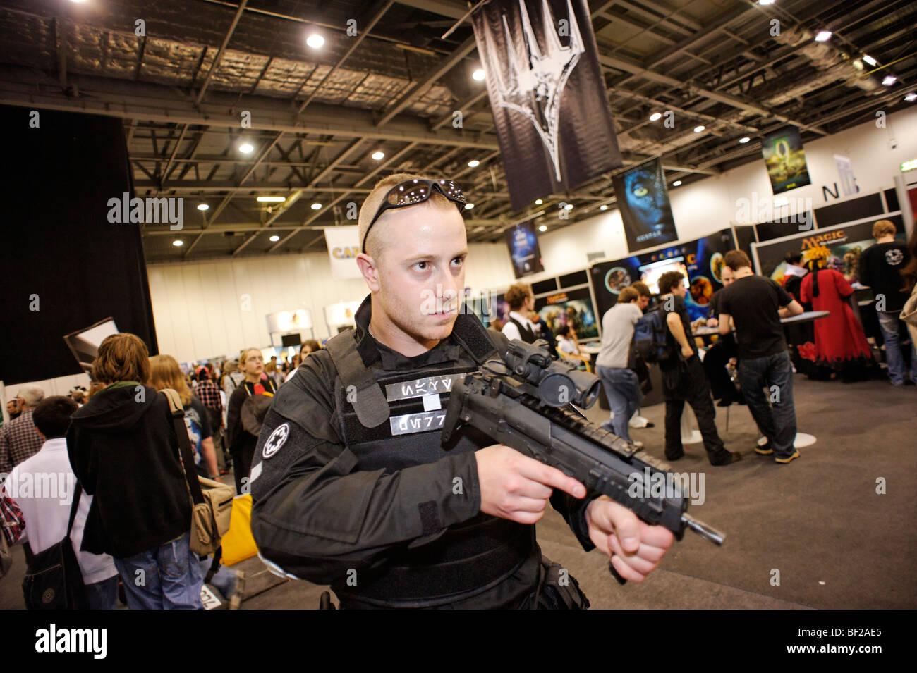 Ventilateur avec faux gun habillé en costume à la patrouille de caractères London MCM expo. Excel. Photo Stock