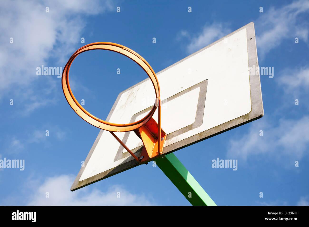 Panier de basket-ball contre un ciel bleu et nuages blancs Photo Stock