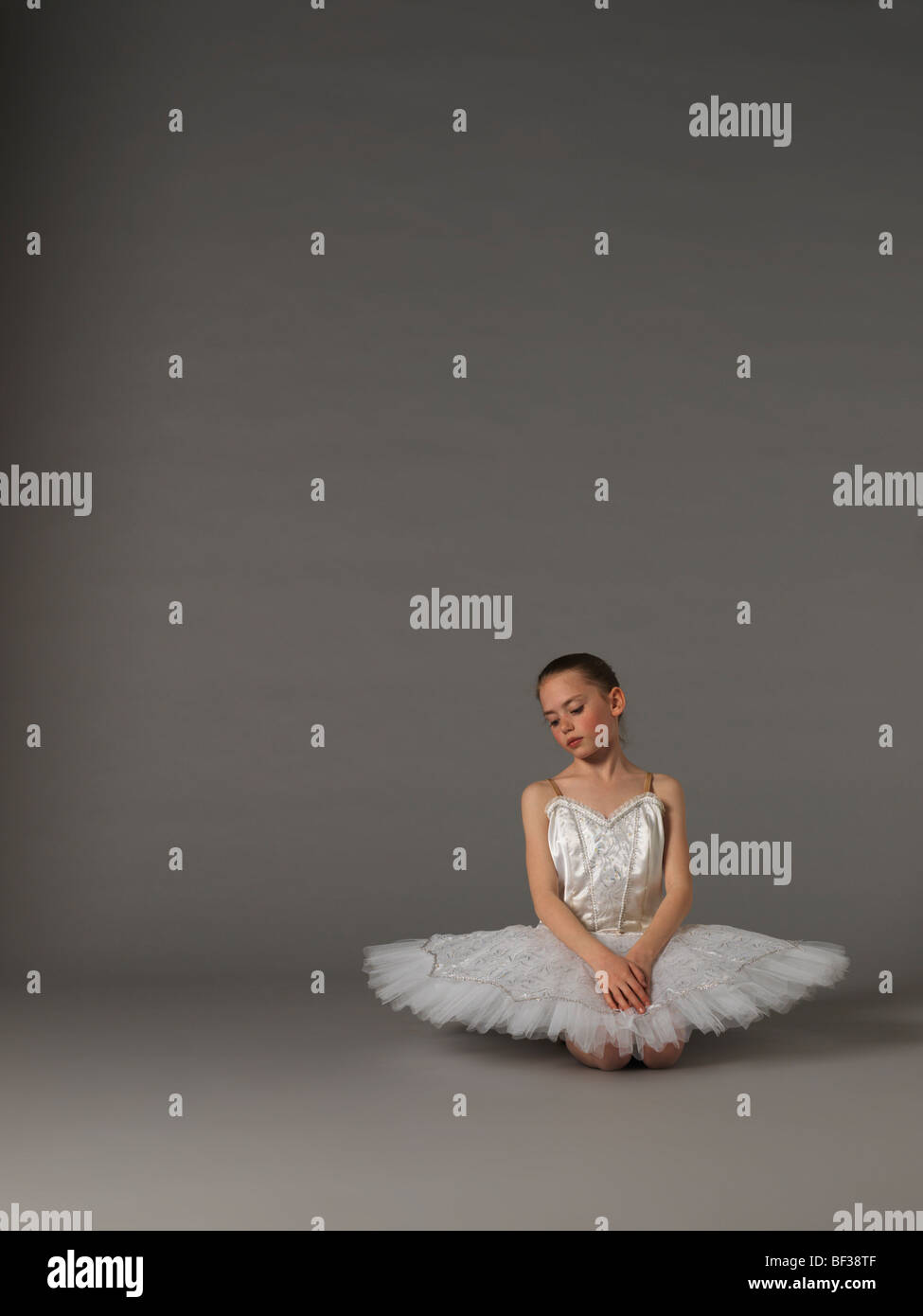 Girl in white tutu s'agenouiller. Banque D'Images