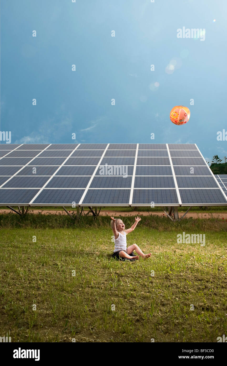 Fille et ballon en avant du panneau solaire Photo Stock