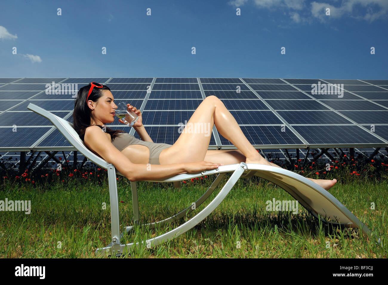 Femme de soleil en face de panneau solaire Photo Stock