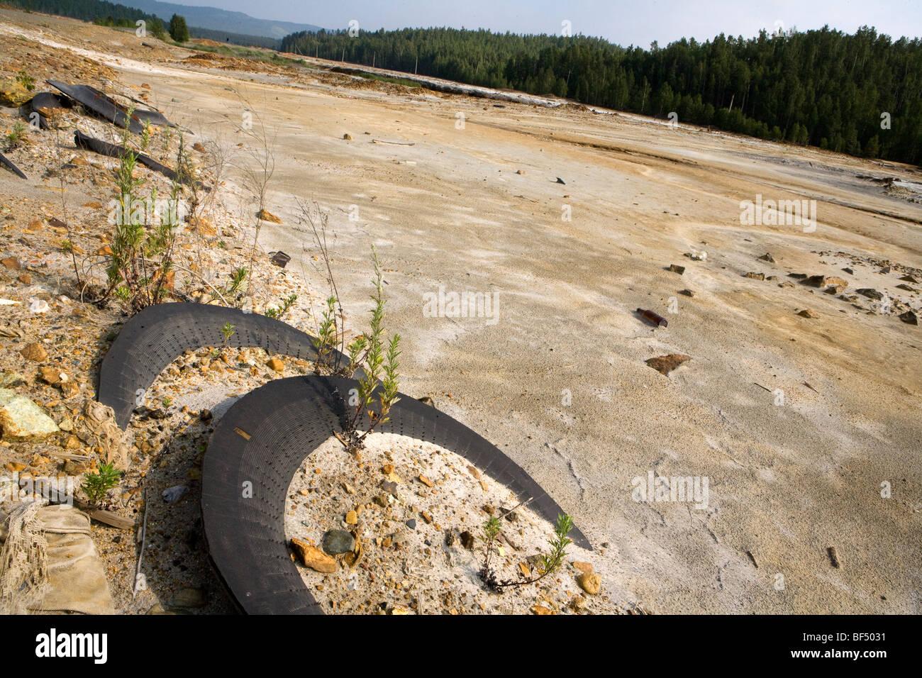 En faisant l'pneus déchets industriels sur les terres polluées, Karabash, Oural, Russie Photo Stock