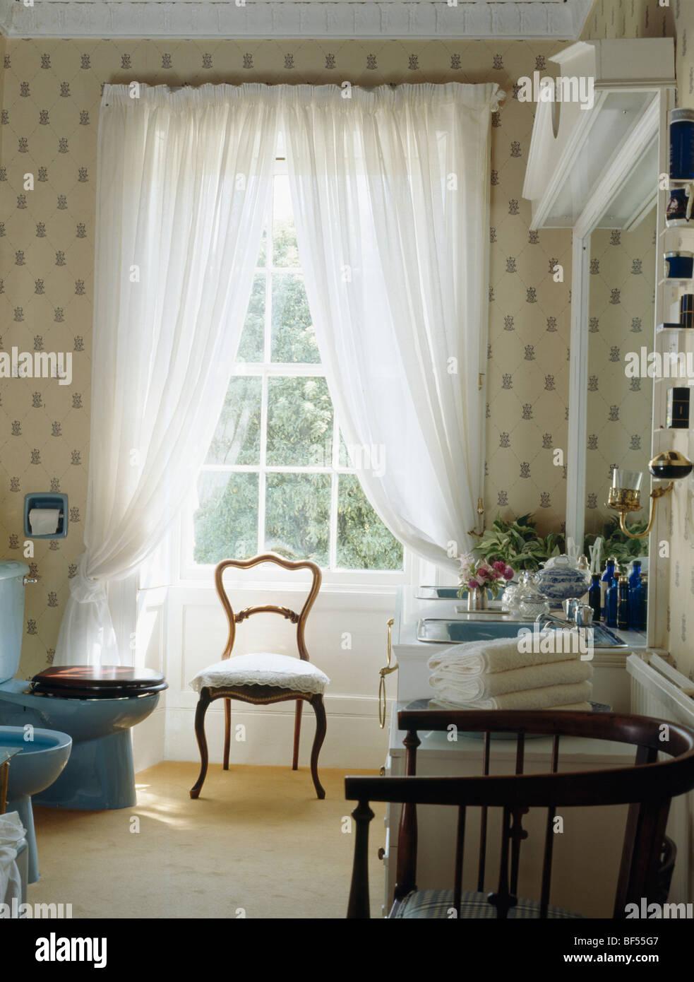 Chaise ancienne en face de grand fenêtre par des rideaux en ...