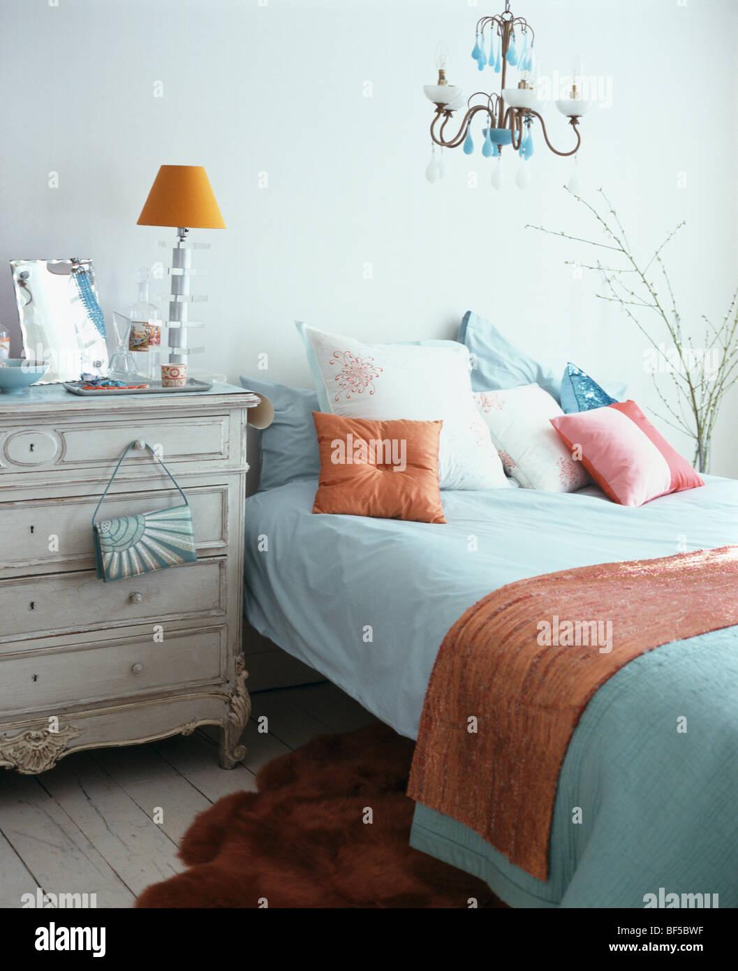 Lampe orange sur la poitrine crème-de-tiroirs à côté de lit ...