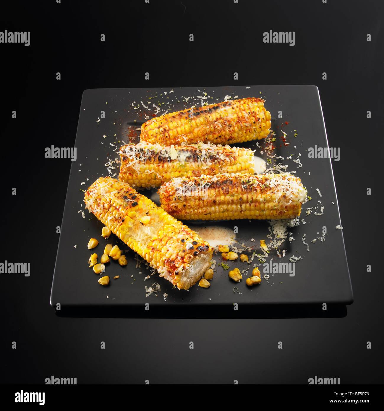 Les épis de maïs au barbecue avec le fromage, le beurre et le piment, sur un fond noir. Photo Stock
