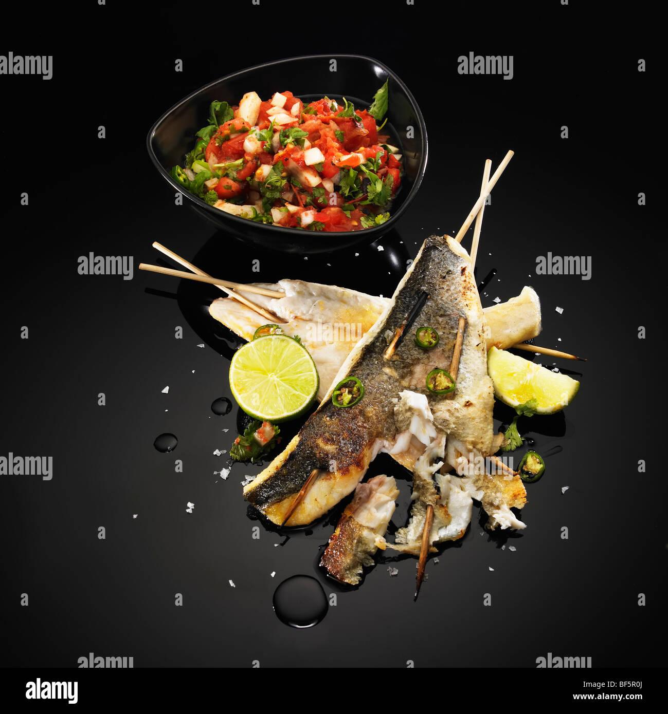 Brochettes de poisson au barbecue avec de la chaux, de piment vert et de la salade, sur un fond noir Photo Stock