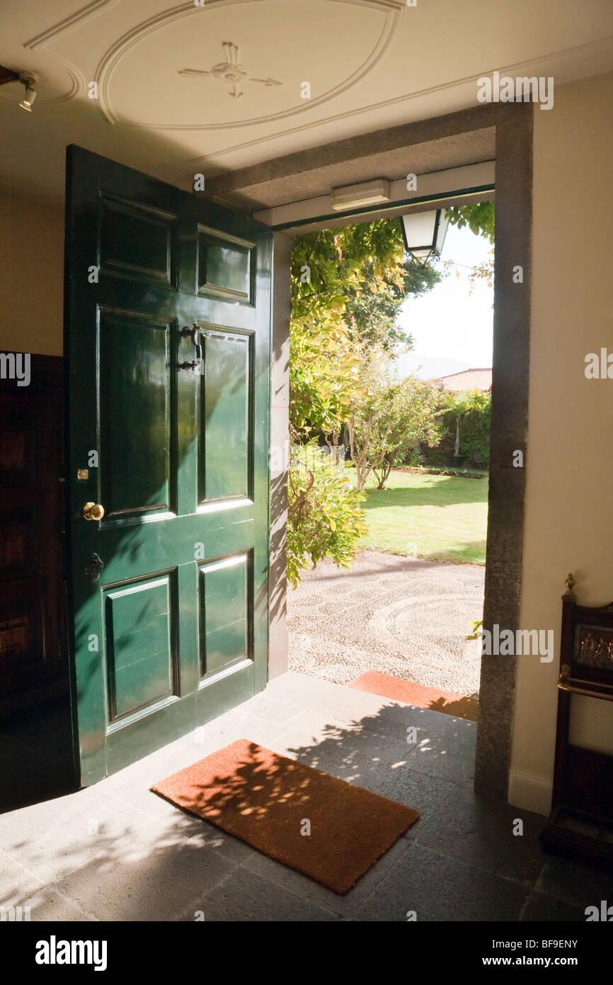 Un livre vert porte ouverte donnant sur un jardin sur une journée ensoleillée Banque D'Images