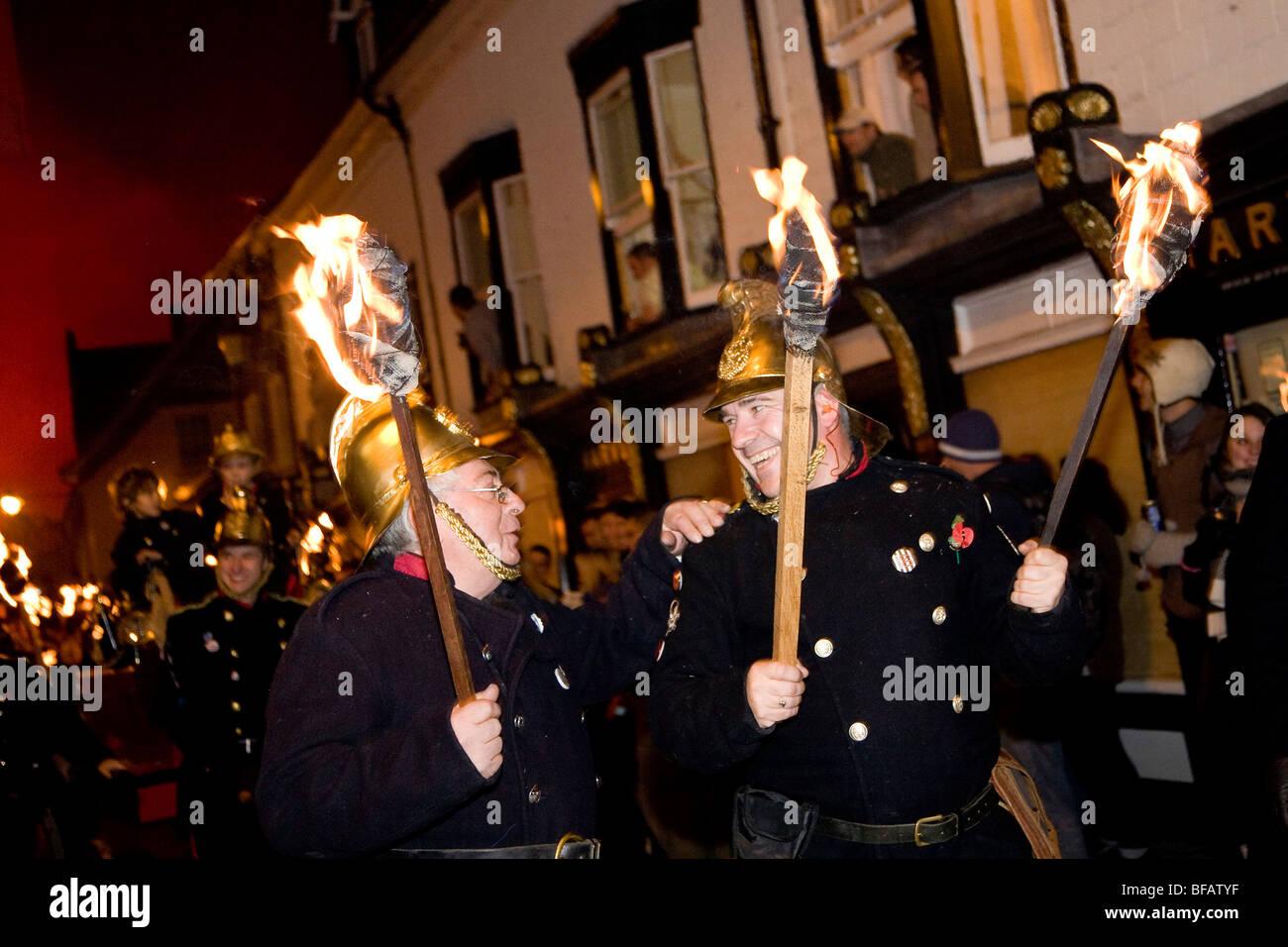 Deux hommes habillés en pompiers vintage comme ils rire marche le long d'une procession aux flambeaux sur Photo Stock