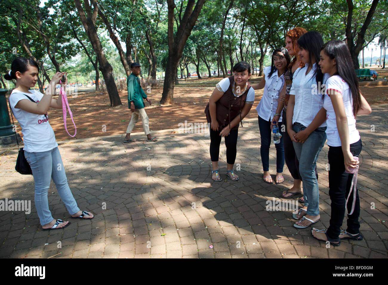 Un groupe de filles indonésiennes posent pour une photo avec un touriste européen dans un parc de Jakarta, Photo Stock