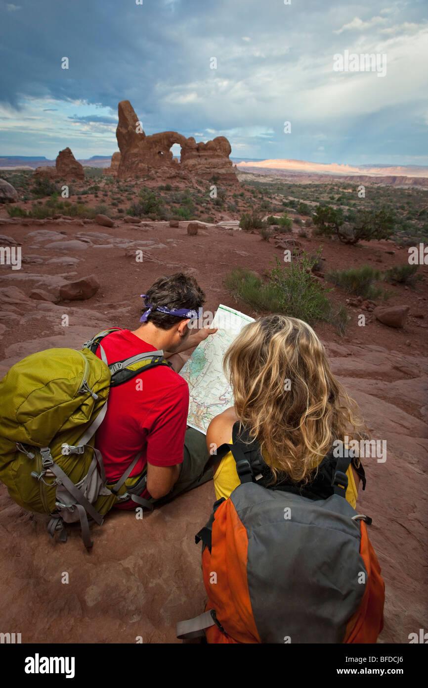 Un couple s'asseoir en regardant une carte à Arches National Park, Utah. Photo Stock