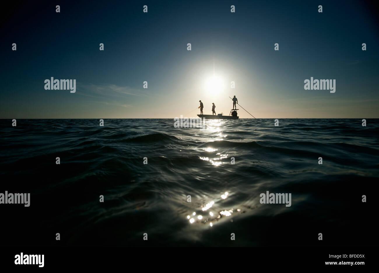 Un couple d'homme poisson pilote un petit bateau en Floride. (Silhouette) Photo Stock