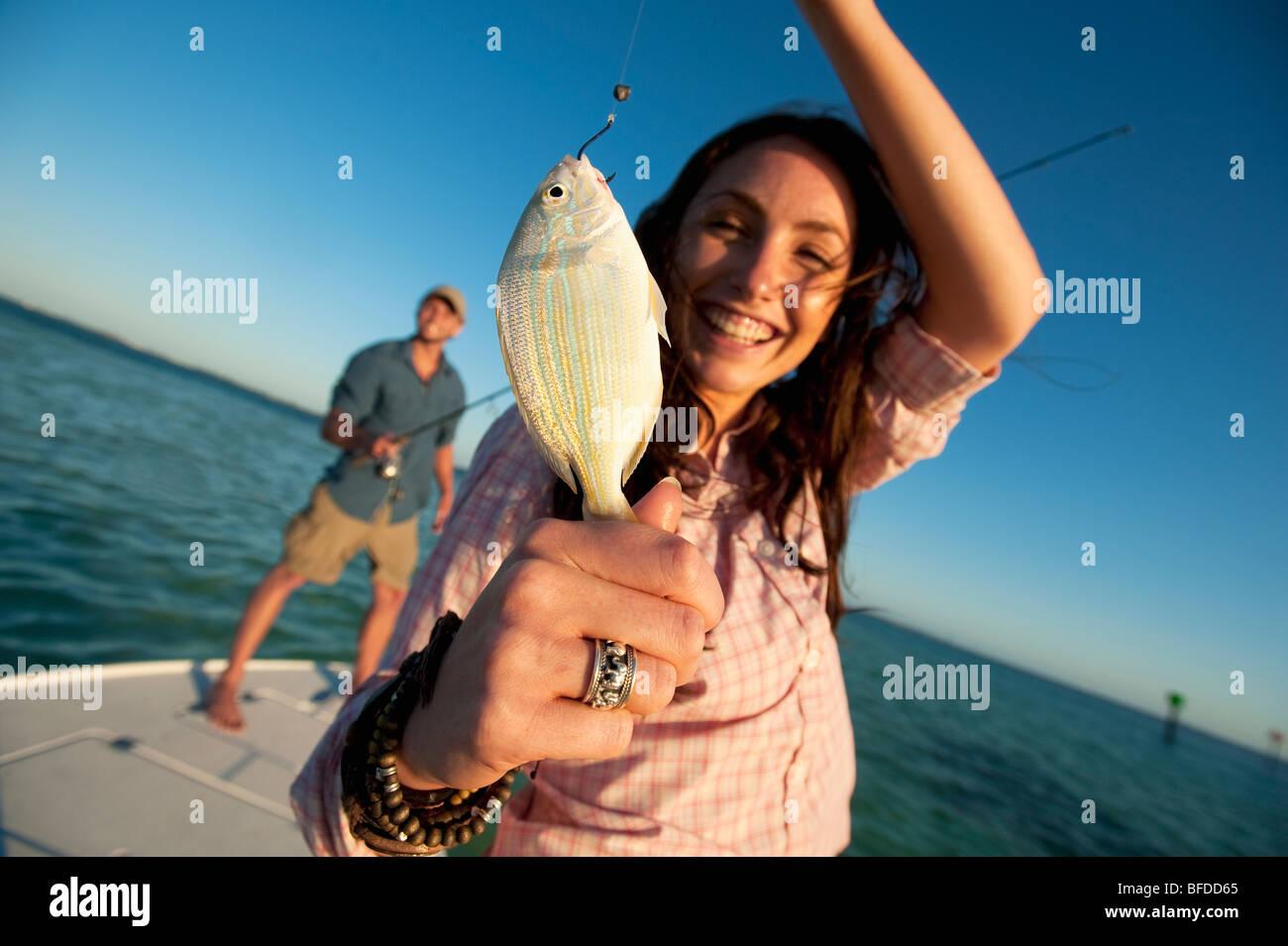 Une femme sourit et nous tend un petit poisson en Floride. Photo Stock