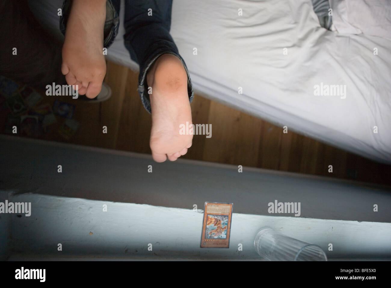 Les pieds du garçon dans sa chambre Photo Stock