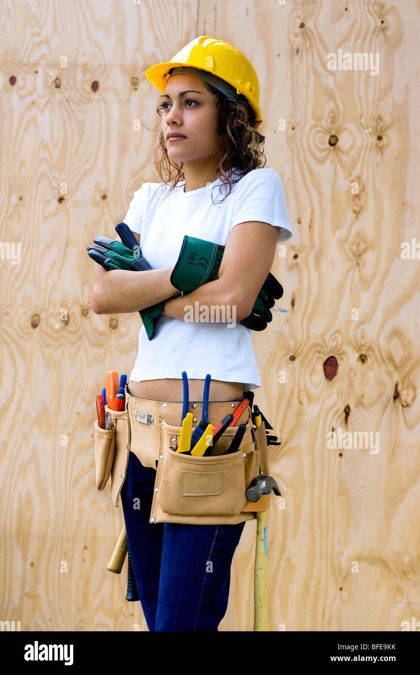 834df97f2226 Jeune femme sur un chantier avec casque et ceinture d outils Photo Stock