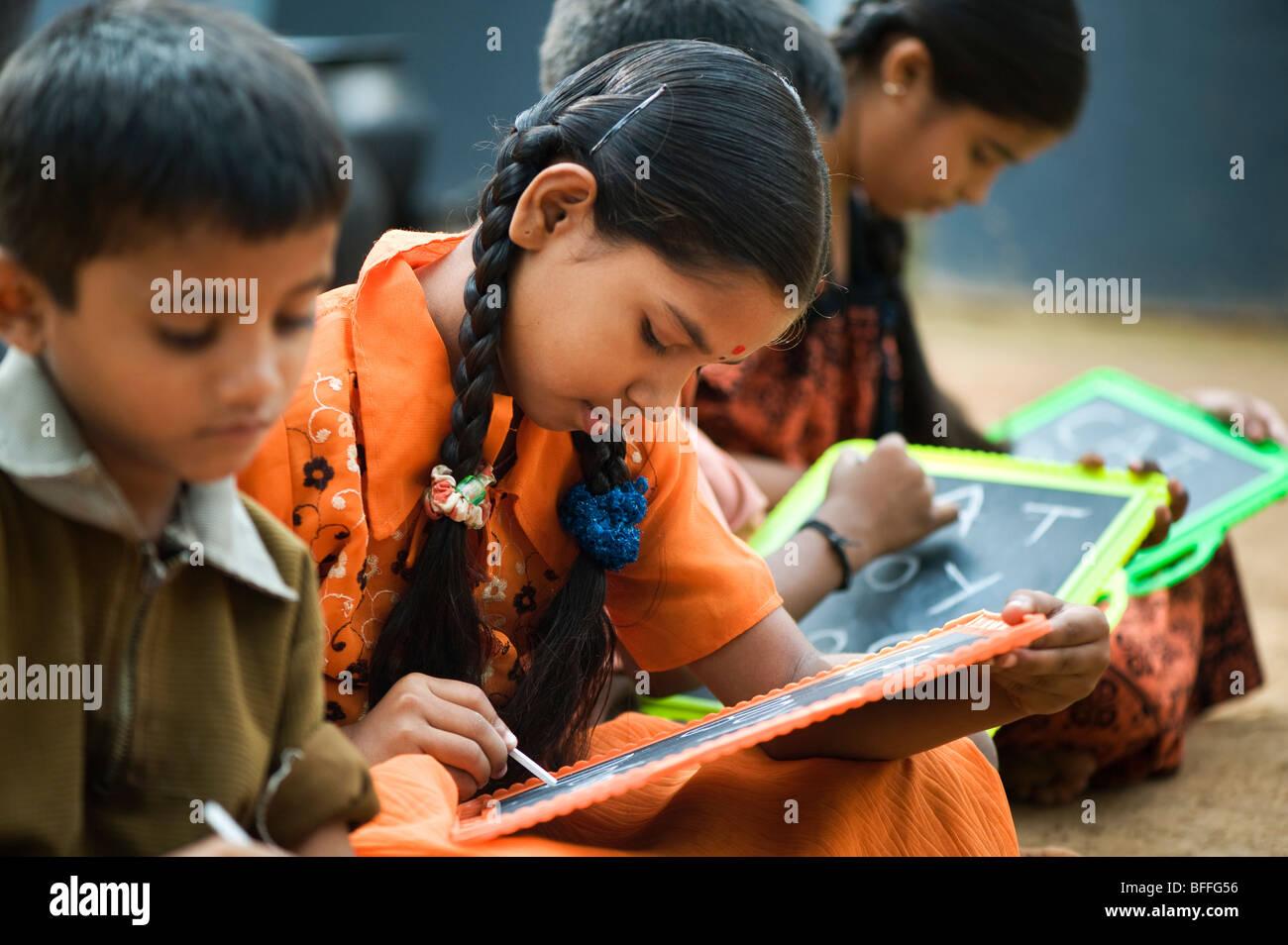 L'école indienne des enfants assis à l'extérieur de l'école écrit sur des tableaux Photo Stock