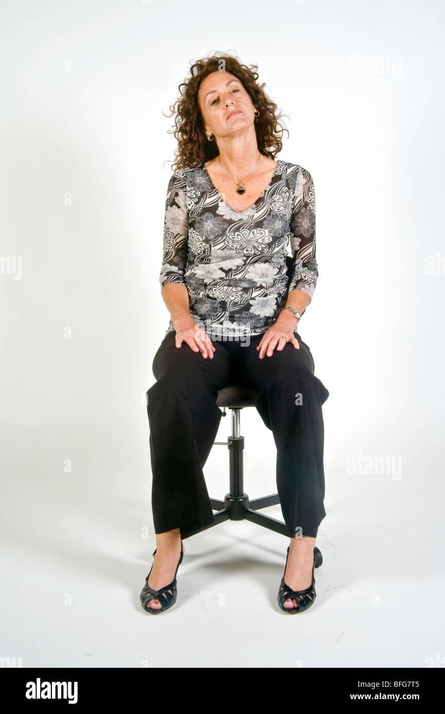 Assis avec les jambes indique une coupure et d'esprit détendu dans cette femme en 'langage du corps'. Photo Stock