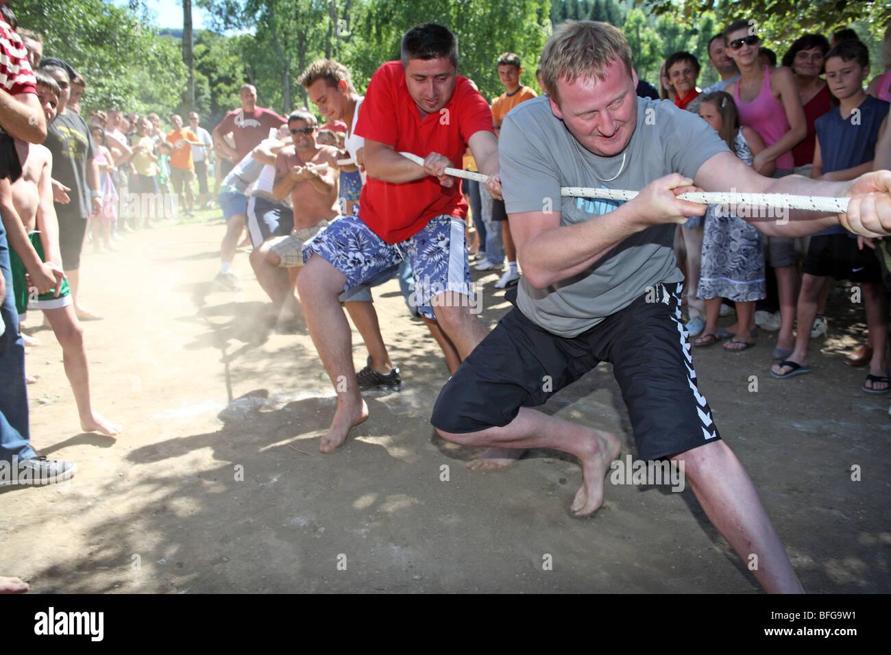 Une équipe de l'homme tire corde sur une plage à un remorqueur de la guerre vu par la foule de spectateurs. Photo Stock