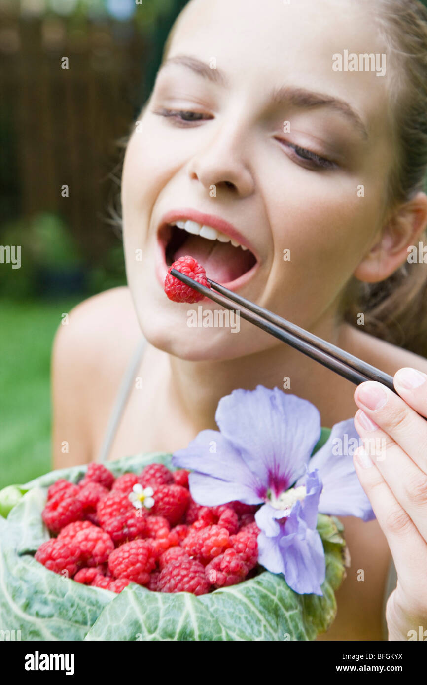 Woman eating framboises au jardin Photo Stock