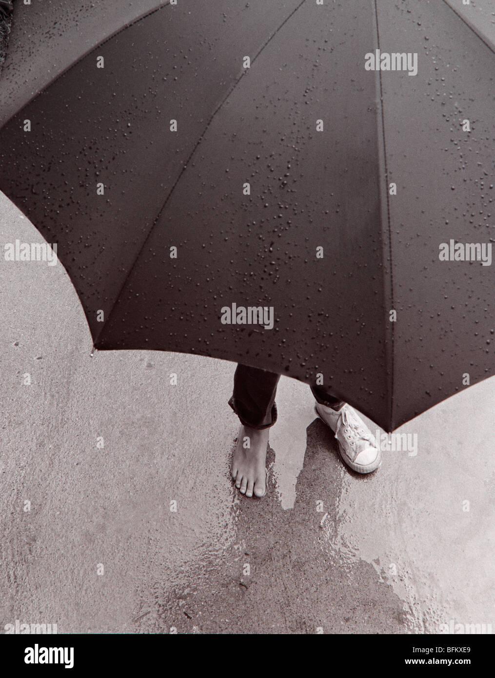Personne debout dans la pluie avec parapluie Banque D'Images