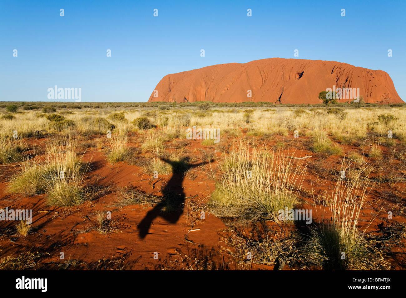 L'Australie, Territoire du Nord, le Parc National d'Uluru-Kata Tjuta. Ombre sauter de joie à Uluru Photo Stock