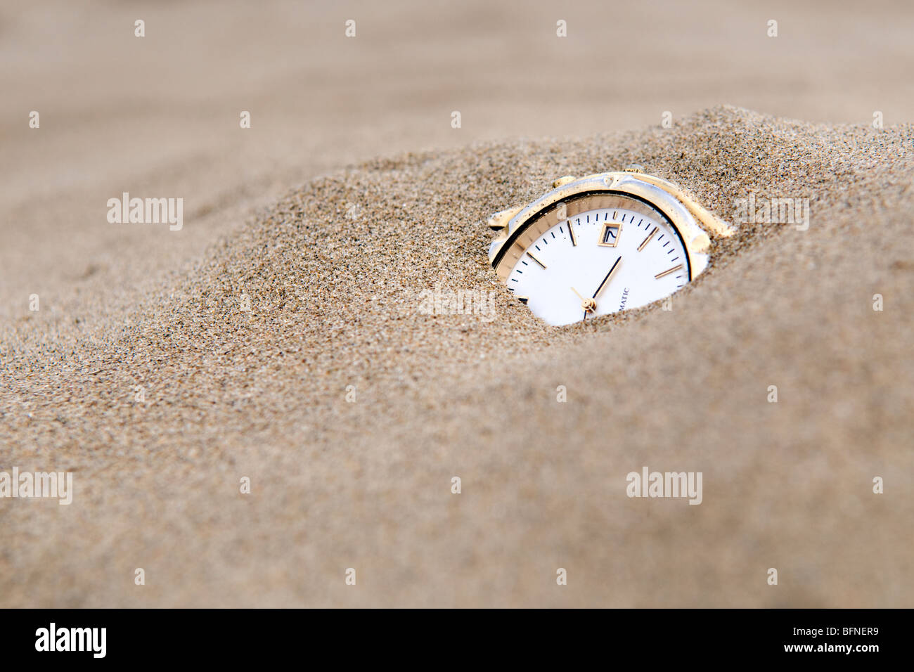 Enterré dans le sable watch prises pour illustrer le concept des sables du temps Photo Stock