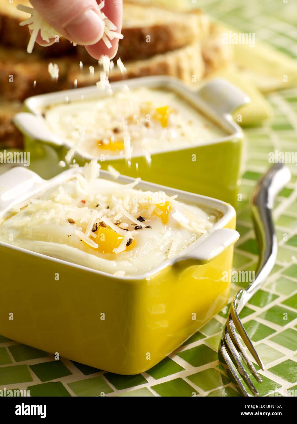 Oeufs cuits au four avec du parmesan saupoudrer Photo Stock