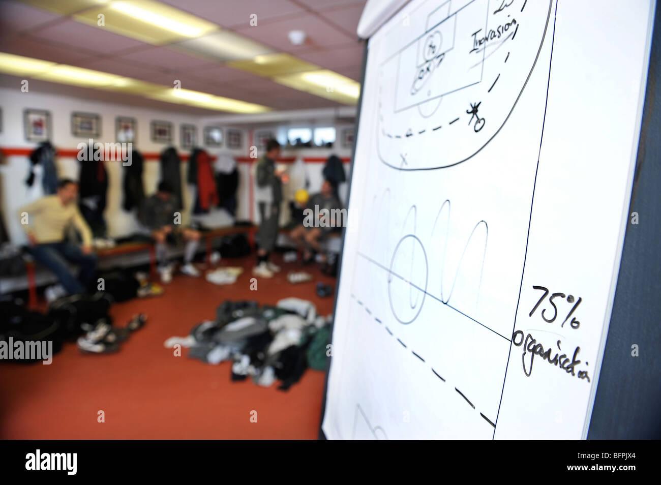 Un tableau blanc avec des footballeurs tactique croquis dans un vestiaire avec kit sales empilés sur le plancher Photo Stock