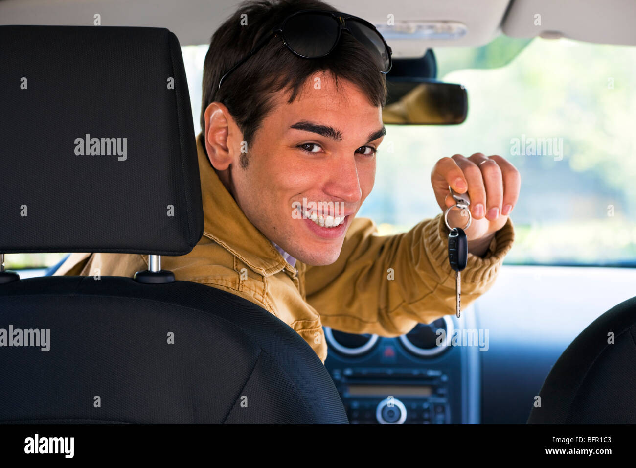 Man in car montrant des clés de voiture Photo Stock