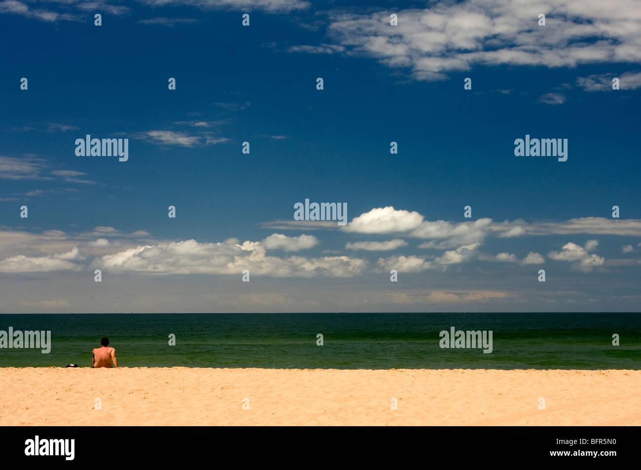 Baigneur solitaire à la recherche à l'horizon sur la plage des pirates Photo Stock